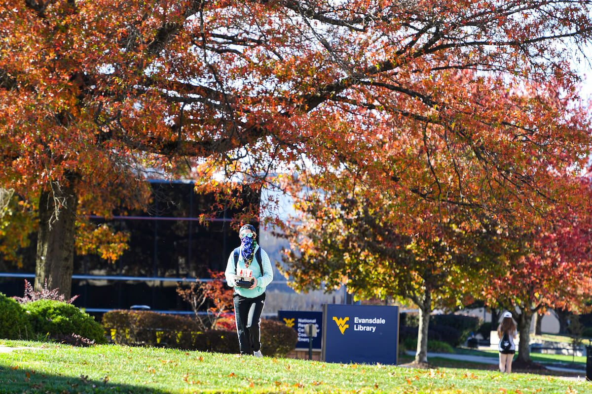 Student in mask walks by Evansdale Library