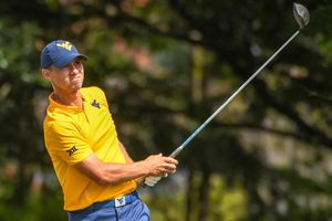 photo of a golfer post-swing wearing gold shirt and blue cap, both with flying WV