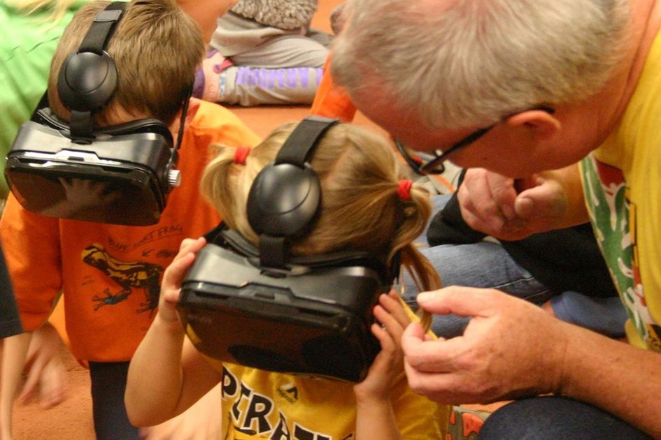A man with gray hair and glasses helps two children with virtual reality equipment