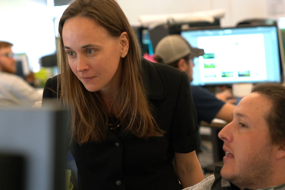 photo of standing woman looking at monitor with seated