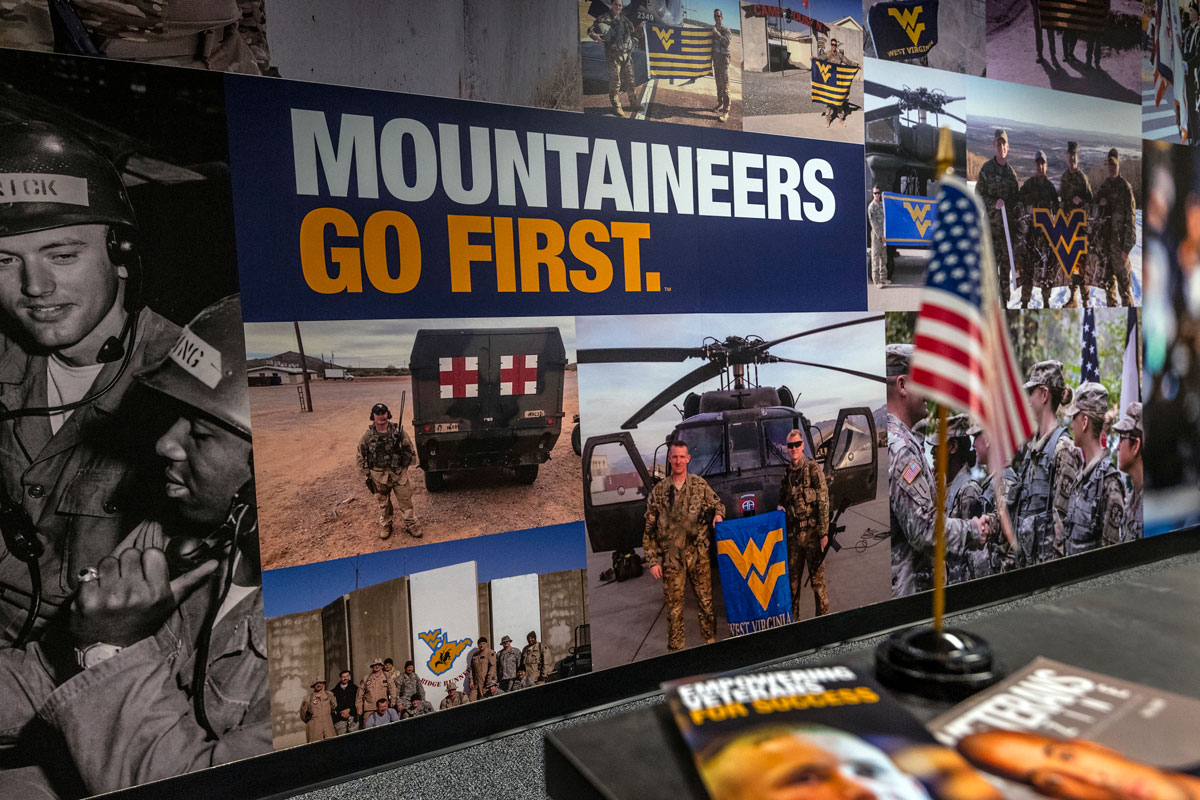 A collage of WVU veteran and military photos with the words Mountaineers Go First overtop of them.