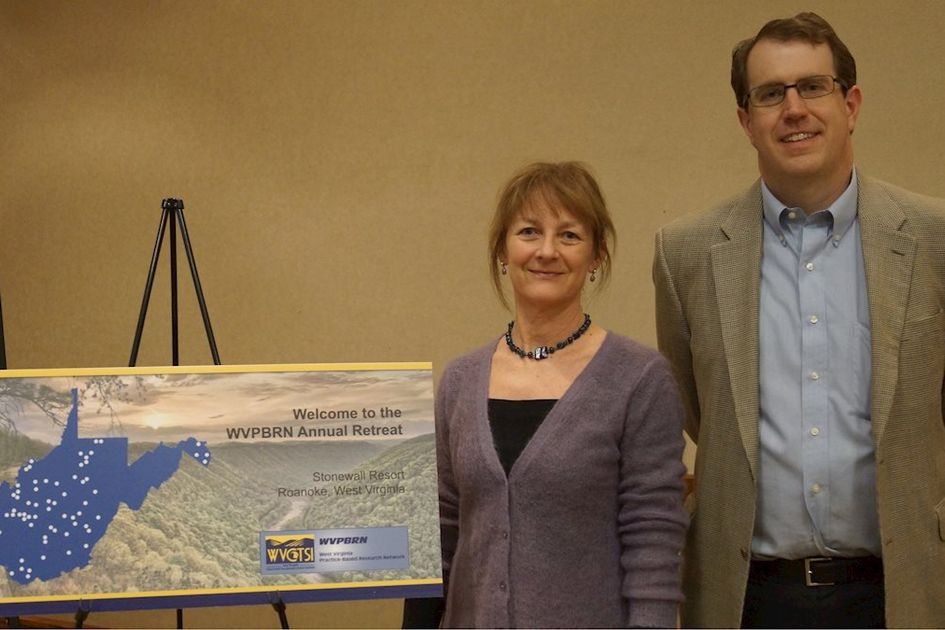 Jennifer Boyd and William Lewis with a blue  map of West Virginia that pinpoints 86 sites of a formal network that studies important health issues in West Virginia.