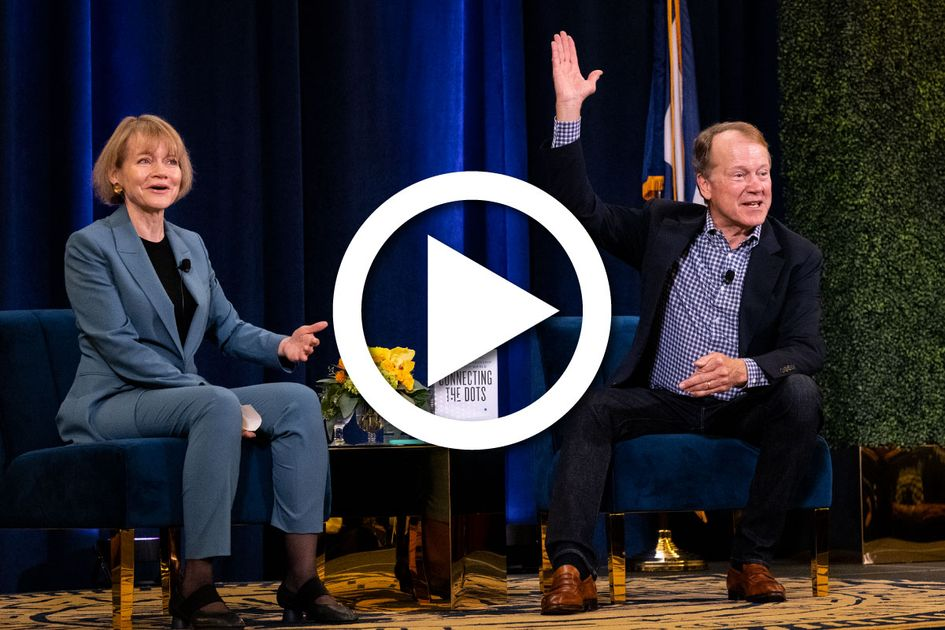 John Chambers sitting on stage for a fireside chat.