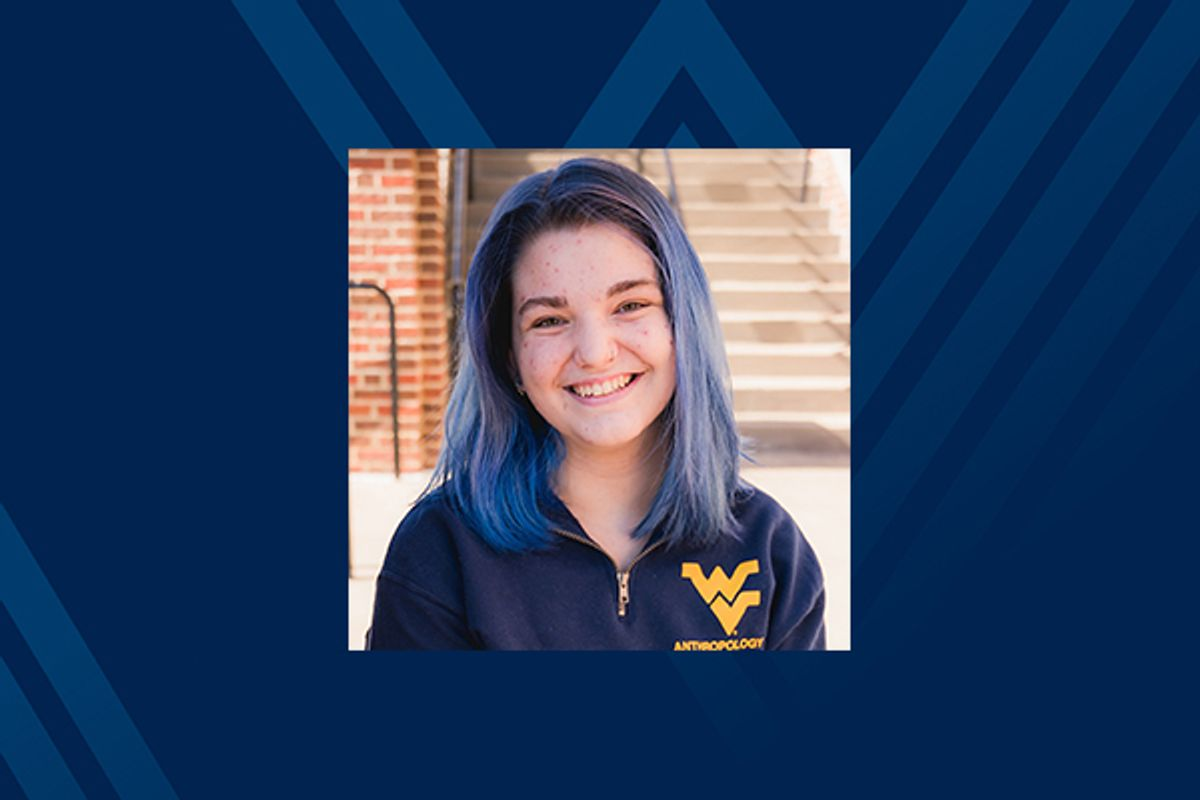 smiling young woman in flying WV shirt on blue background