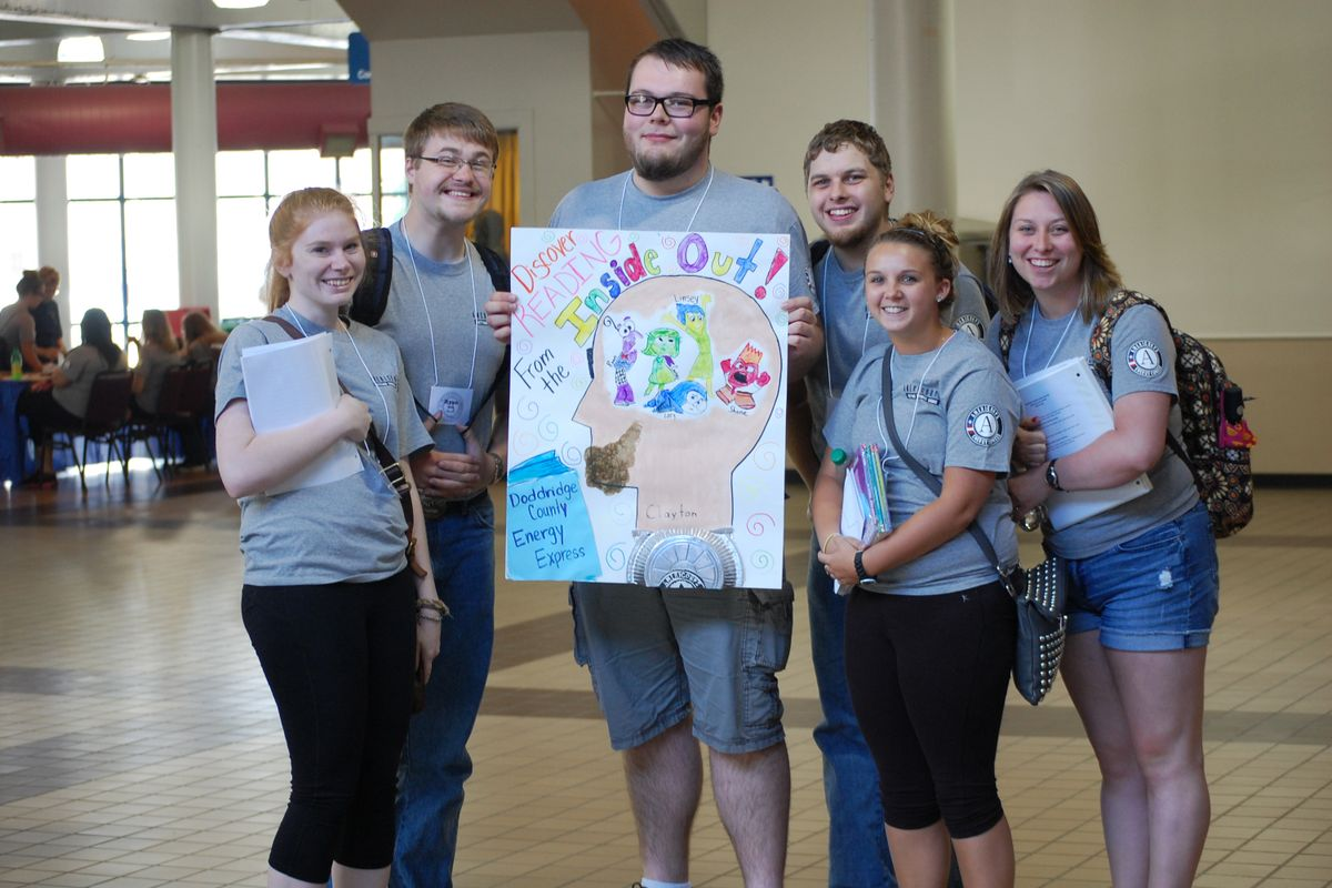 Energy Express mentors gather around a poster promoting reading