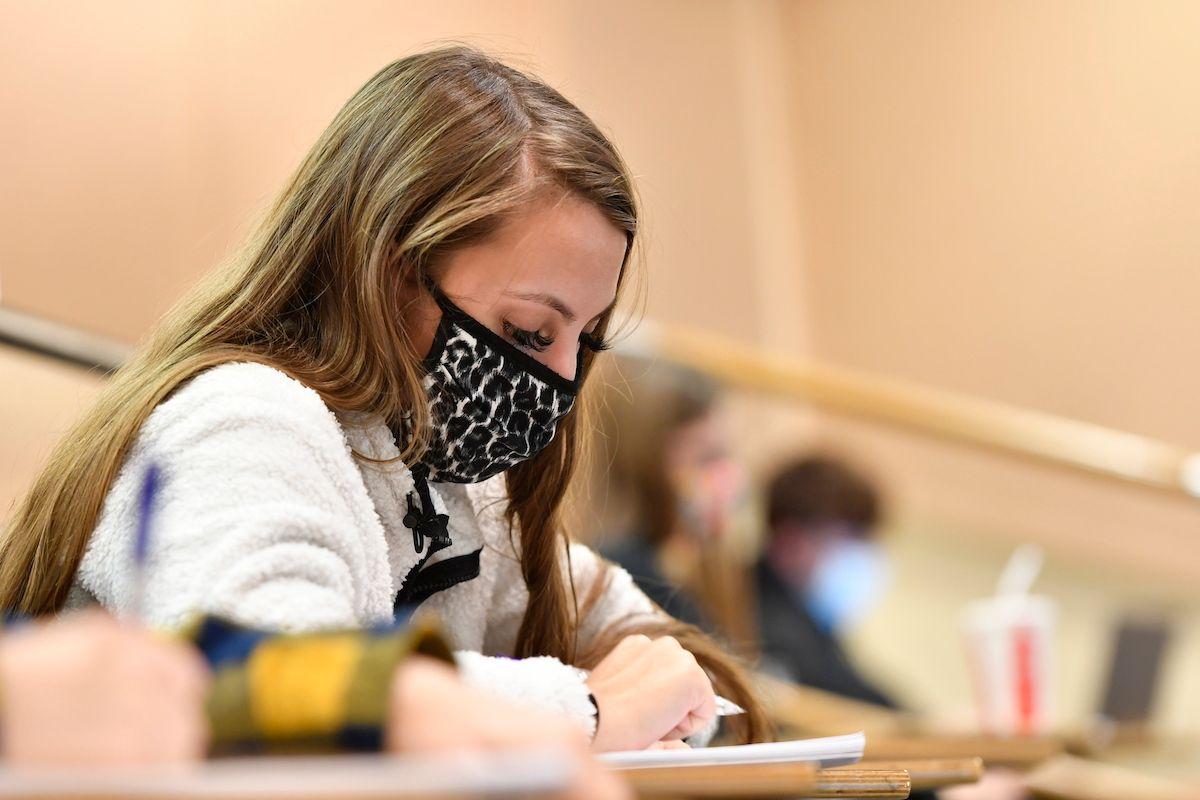 woman wearing mask taking notes
