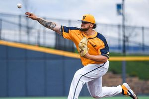 baseball player pitches ball with right hand wearing gold and blue jersey and white pants