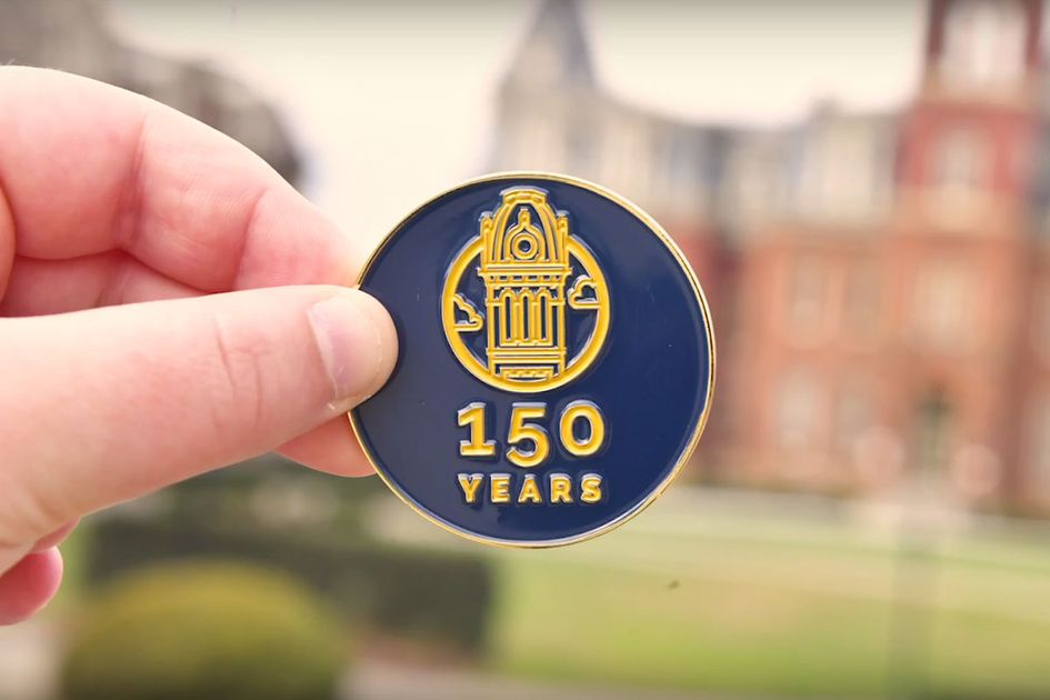 A hand holding out a blue and gold WVU coin with the 150 Years logo on it with Woodburn Hall blurred in the background.