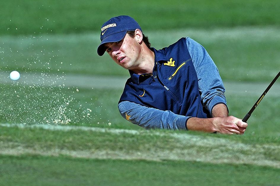 A golfer hits a ball out of the sand
