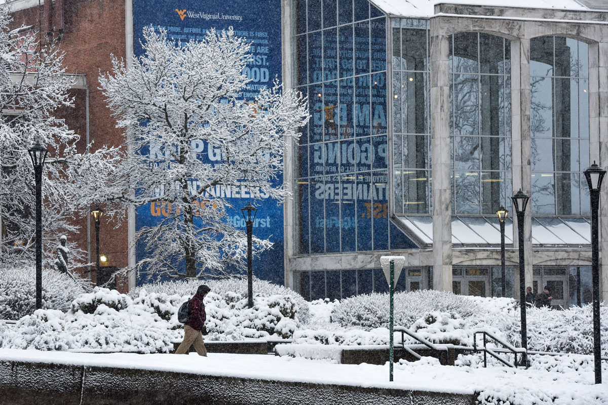 A student walking alone through a snow covered campus.
