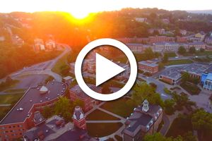 An arial shot of campus with a video play button over top.