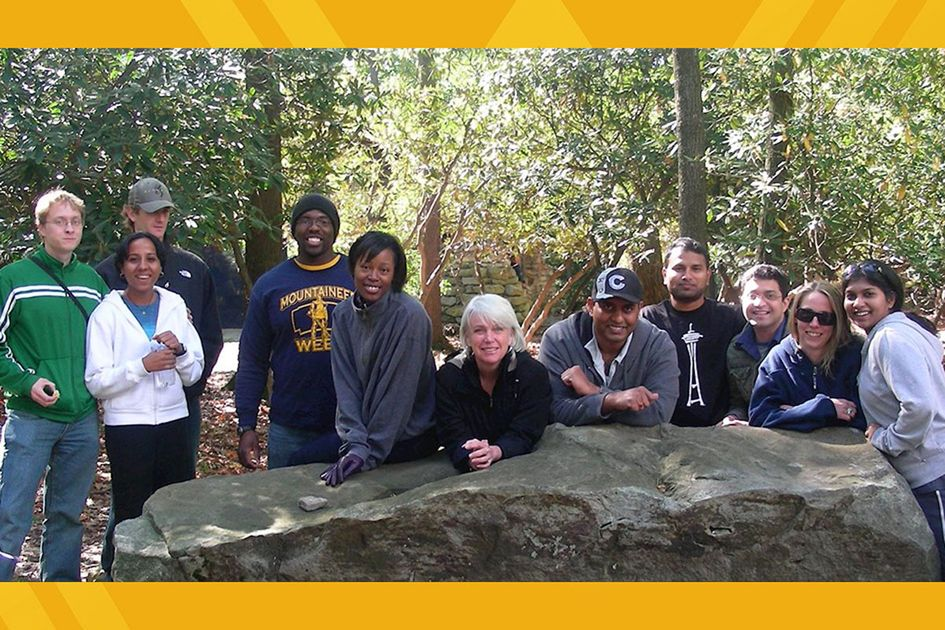 Members of the WVU STEM Ambassadors posing on a rock in the woods.