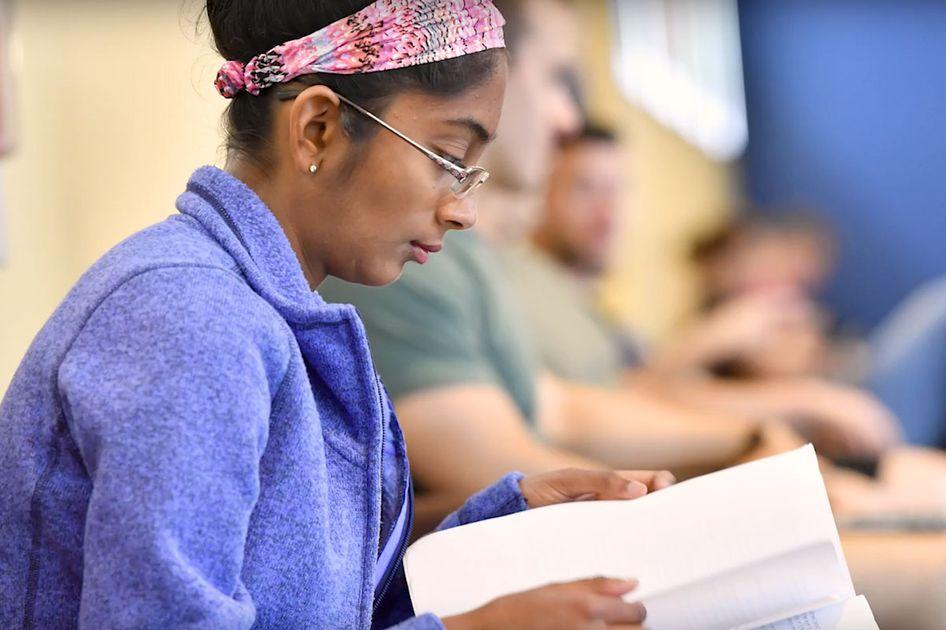 A WVU student reading a book.