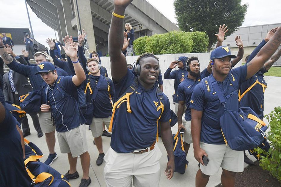 The football team outside the stadium waving at fans.