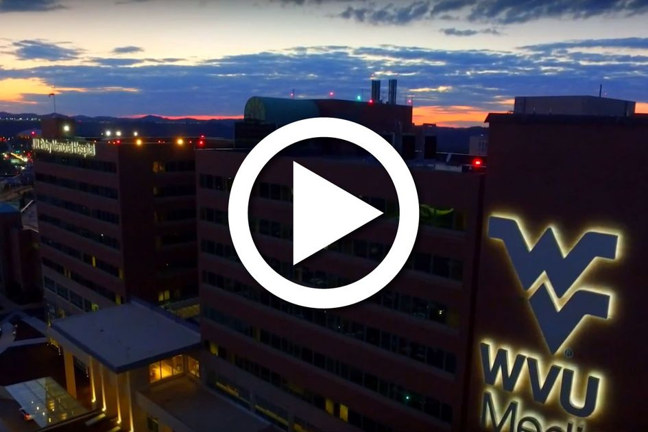 The WVU Medicine hospital building with the sun setting behind it.