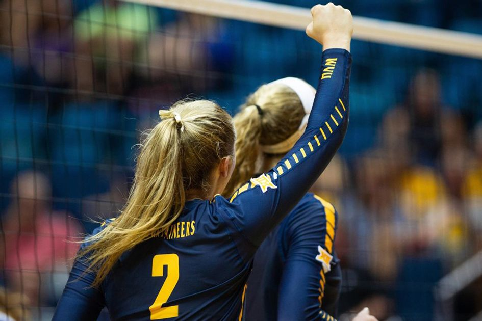 A volleyball player raises her fist
