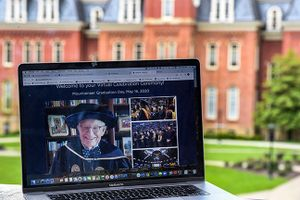 laptop screen with man in commencement regalia in front of large brick building