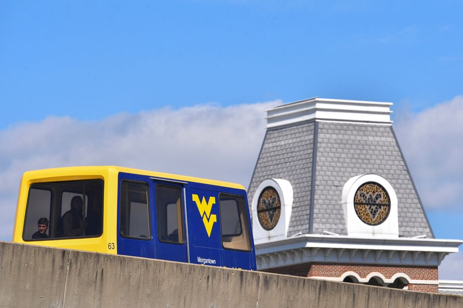 A PRT on the tracks with a WVU building in the background.