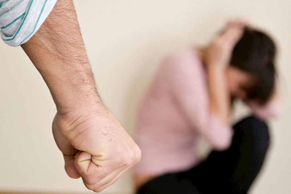 A photo of a man clinching his fist angrily as a scared women sits on the floor in the distance.