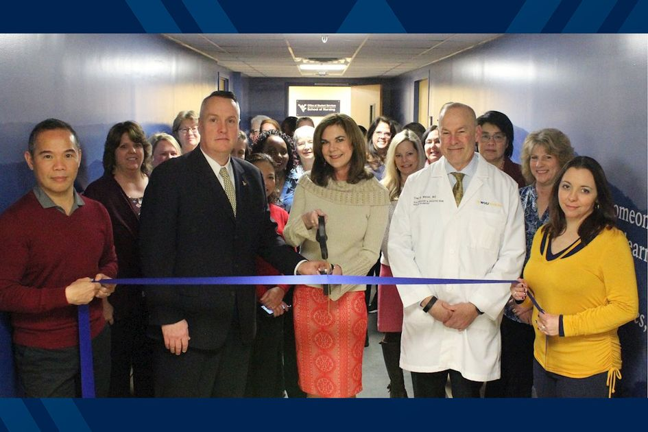 A group of people in the School of Nursing cutting a ribbon.