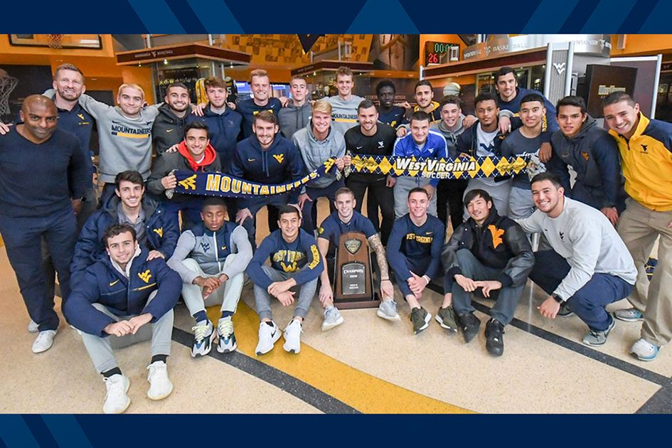 The men's soccer team posing with trophey.