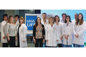 A group of medical professionals and support staff stand in two groups in front of a sign that says LEGS LIFE