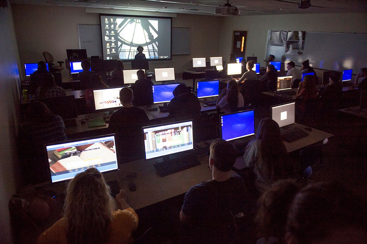 Photo of a darkened classroom with several computer screens, a larger screen at the front of the room