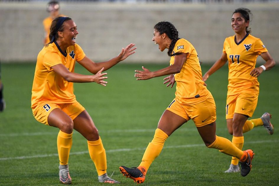 Photo of three women in gold soccer uniforms celebrate on the field