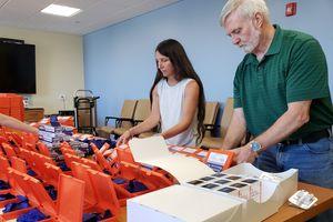 Two people assembeling Naloxone kits