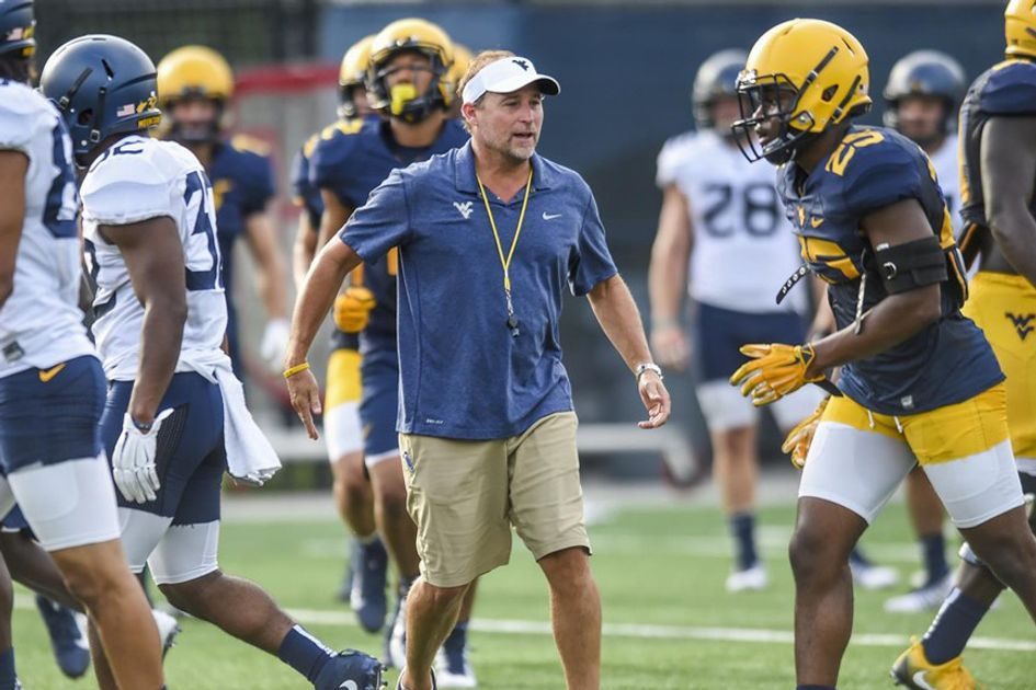 WVU Football coach Dana Holgersen on the field with players during spring/summer practice