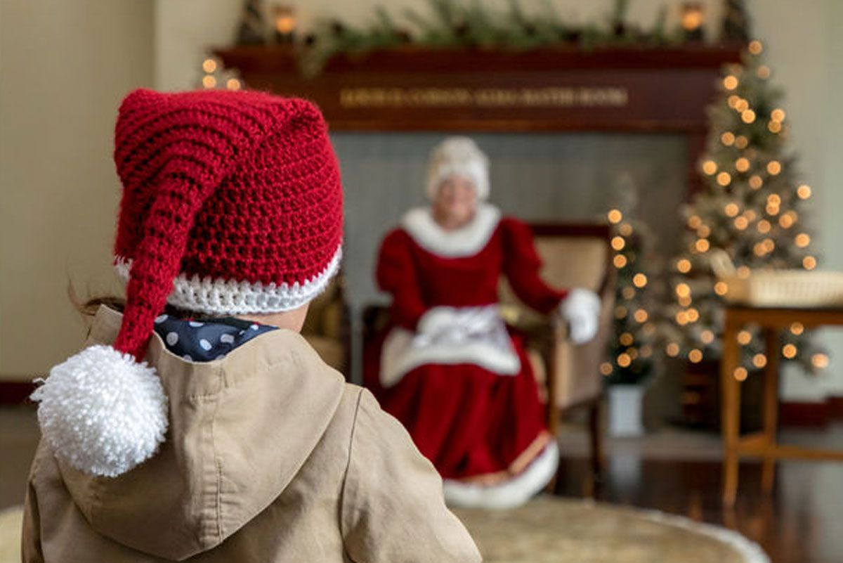 A young boy approaching Mrs. Clause seated on a chair.