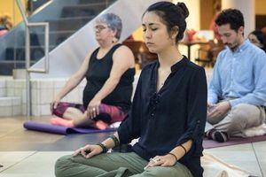few people sitting cross legged meditating