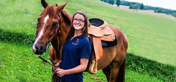 student with saddled horse