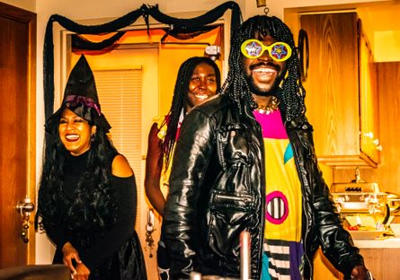 Image of three people laughing during Halloween party.