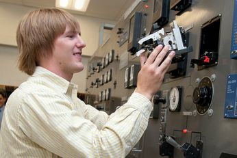 An image of a student working with an industrial circuit breaker