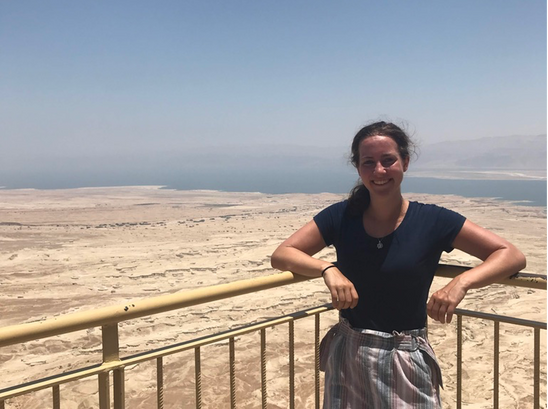 Talia Buchman, an anthropology major, posing in Israel on a railing. She is wearing a blue top, shorts, and is smiling. She has brown hair and blue eyes and is skinny. The terrain behind her is a dusty desert and it mets the blue muddled sky.