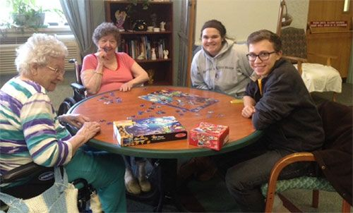 Students helping nursing home residents with jig-saw puzzle.
