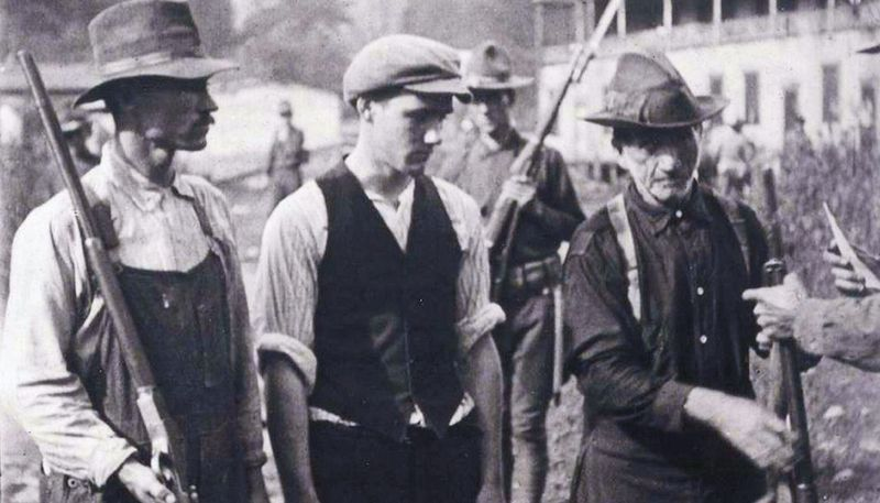 A black and white photograph of three miners