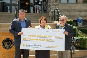 Shawn Ball, Carolyn Long and Gordon Gee hold a check during a presentation.
