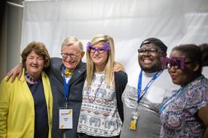Campus President Carolyn Long and WVU President Gordon Gee pose with students at a photo booth.