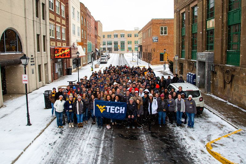 Hundreds of student and staff volunteers stand on Neville street in Beckley, proudly displaying the WVU Tech flag, wisps of snow swirling around them and obvious cheer in their hearts.