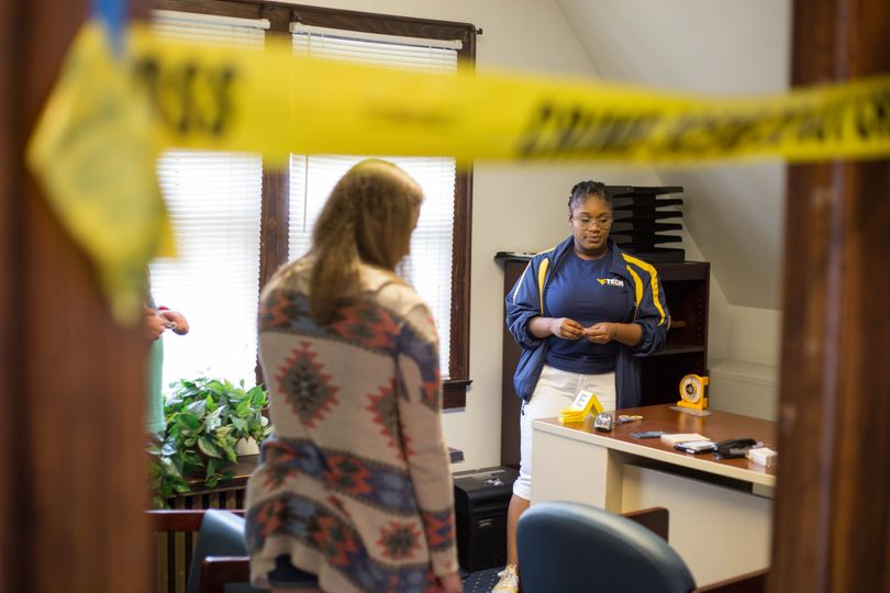 From a first-person perspective, we see a door jamb with crime scene tape running across it. Behind, two investigators stand next to a desk discussing their findings.