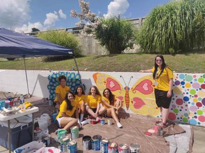 A group of WVU Tech students in gold t-shirts paint during the Golden Bears Give Back Day of Service, 2019