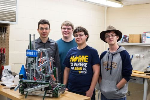 Student from the Vex robotics team stand with Monty1.