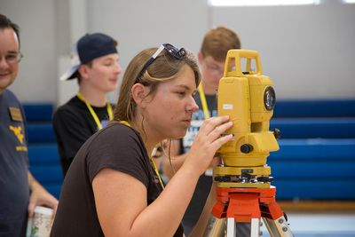 A camp STEM student uses a total station during the civil engineering class.