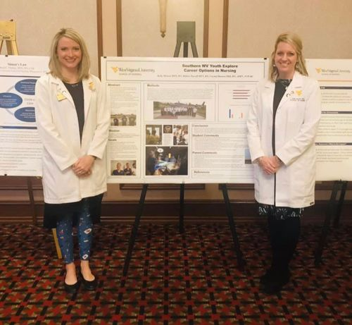 WVU School of Nursing faculty members Hillary Parcell MSN, RN and Kelly Morton MSN, RN stand in front of their presentation poster at the WV Nurses Association Policy Summit.