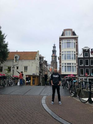 Cody Walker stands for a photo in the city of Amsterdam wearing a TRIO shirt.