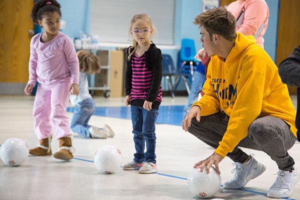 In a gym, a male WVU Tech student crouches to talk to two Head Start students, his hand resting on a small, white soccer ball. To his left, two four-year-old girls listen to him as they wait anxiously to kick the soccer balls at their feet.