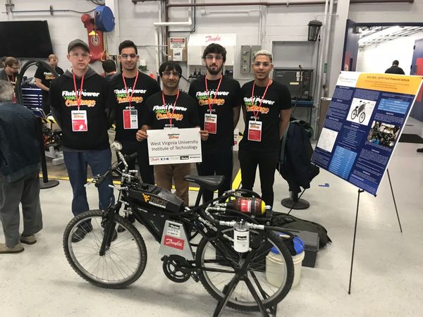 The team stands alongside their bike at a competition in Ames, Iowa.
