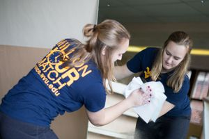 A WVU Tech students cleans a mirror during an MLK Day service project for the Women's Resource Center in Beckley